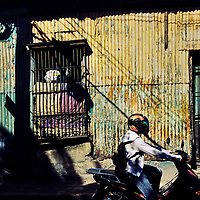 A Salvadoran man rides a motorcycle in front of a low class house, designed by using Spanish colonial architecture elements, built in a working class neighborhood of San Salvador, El Salvador, 15 November 2016.