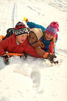 Friends age 7 through 10 falling off snow sled. St Paul Minnesota USA