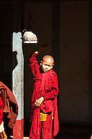 A young monk in the Nang Yone Monastery near Hsipaw, Myanmar, stands on tiptoe to ring the bell which summons the whole community to lunch in the dining hall.