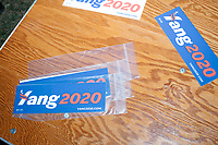"""Campaign stickers lay on a table as entrepreneur and Democratic presidential candidate Andrew Yang speaks to a large crowd in Cambridge Common near Harvard Square in Cambridge, Massachusetts, on Mon., September 16, 2019. Yang's unlikely presidential bid is centered on his idea for a """"Freedom dividend,"""" which would give USD$1000 per month to every adult in the United States. After appearing in three Democratic party debates, Yang has risen in polls from longshot candidate to within the top 10."""