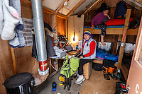 Volunteer comms Katy Kerris (on bunk) and Valerie Saiki inside the comms shack at the Ophir Checkpoint on Thursday March 10 during Iditarod 2016.  Alaska.    <br /> <br /> Photo by Jeff Schultz (C) 2016  ALL RIGHTS RESERVED