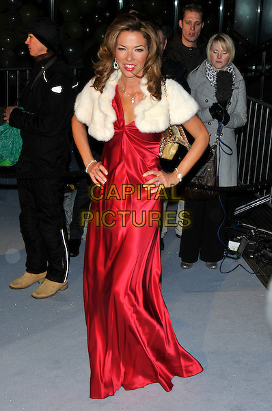 HEATHER KERZNER .Attending The Love Ball during London Fashion Week, the Roundhouse, Chalk Farm Road, London, England, UK, .February 23rd 2010..arrivals full length long maxi red dress hands on hips white fur shrug cape gold shoulder strap bag silk satin .CAP/PL.©Phil Loftus/Capital Pictures.