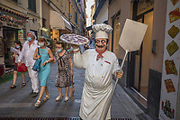 Italy. Liguria Region. San Remo. Street in the town center. The statue of a pizzaiolo carrying a big delicious pizza. A group of people wearing masks to protect themselves from the Coronavirus (also called Covid-19). The safety sanitary measures advocate people to stand apart in order to avoid close contact and potential contamination by coronavirus. Liguria is a region of north-western Italy. Sanremo or San Remo is a city and comune in the Province of Imperia. 23.07.2020 © 2020 Didier Ruef