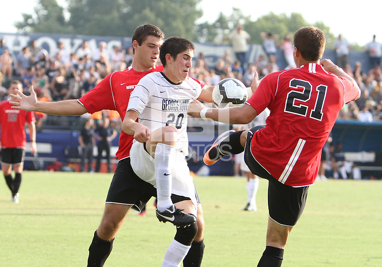 Andy Riemer #20 of Georgetown University caught between Don Anding #12 and Josh Semerene #21 of Northeastern University during an NCAA match at North Kehoe Field, Georgetown University on September 3 2010 in Washington D.C. Georgetown won 2-1 AET.