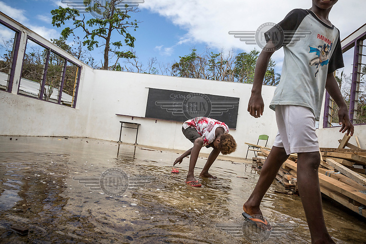 Two pupils walk through shallow water that has been left behind by Cyclone Pam as it swept over their island. Pupils at this school are not able to return to school since most of their study materials are lost and their classroom was largely destroyed by the storm. On the blackboard, someone has written: 'Cyclon [sic] Pam is coming, run for your life.'<br /> Cyclone Pam, a tropical storm that hit the Pacific island nation of Vanuatu on 13 March 2015, is considered one of the worst natural disasters to affect the country. Over 15 people died in the storm and winds up to 165 mph (270 km/h) caused widespread damage to houses and infrastructure.