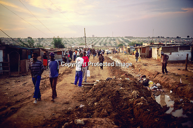 Residents walk along a damaged road as the sun sets in Diepsloot, a poor township outside Johannesburg, South Africa.