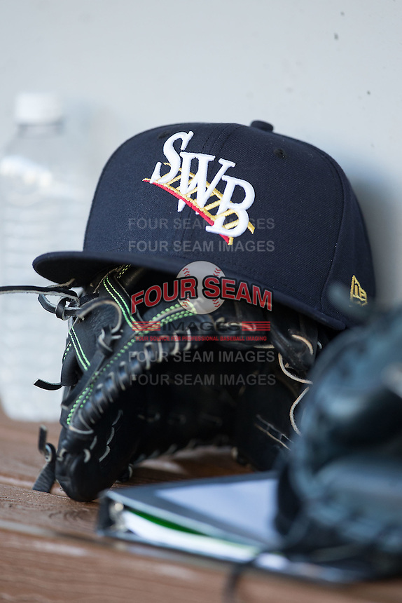 A Scranton/Wilkes-Barre RailRiders cap sits on top of a glove in the visitors dugout during the game against the Charlotte Knights at BB&T BallPark on July 20, 2016 in Charlotte, North Carolina.  The RailRiders defeated the Knights 14-2.  (Brian Westerholt/Four Seam Images)