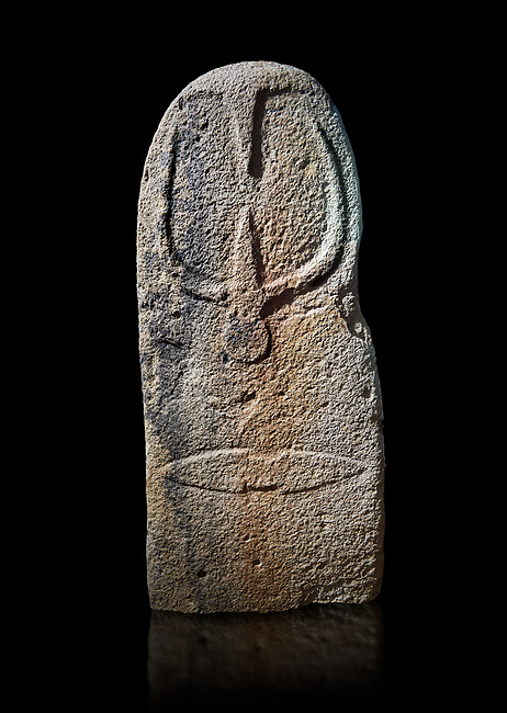 Late European Neolithic prehistoric Menhir standing stone with carvings on its face side. The representation of a stylalised male figure starts at the top with a long nose from which 2 eyebrows arch around the top of the stone. below this is a carving of a falling figure with head at the bottom and 2 curved arms encircling a body above. at the bottom is a carving of a dagger running horizontally across the menhir. Excavated from Bau Carradore II, Laconi. Menhir Museum, Museo della Statuaria Prehistorica in Sardegna, Museum of Prehoistoric Sardinian Statues, Palazzo Aymerich, Laconi, Sardinia, Italy. Black background.