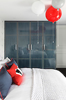 A glossy wardrobe made of stained wood and metal provides ample storage in this child's bedroom