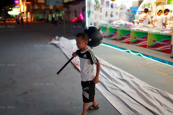 A boy carries an inflatable hammer through the carnival grounds of the Qingdao (Tsingtao) Beer Festival in Qingdao, China on 27 August, 2011. Named after the locally brewed Tsingtao Beer, one of China's most famous exports, the festival has grown from a local binge drinking feast to an internationally known festival.