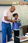 Berkeley, CA African American male teacher and student reading aloud to students in fifth grade classroom