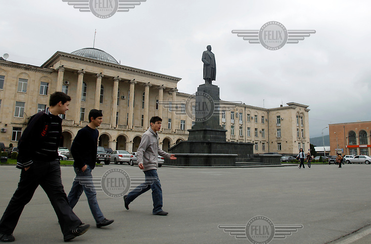 Three young boys walk past a statue of Joseph Stalin that stood outside the Town Hall until being removed in 2010 as part of Georgia's de-Sovietisation policy.