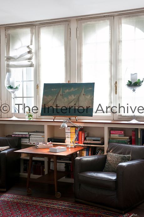 Bookcases built along the wall and under the window are both space-saving and the perfect height for access from a pair of comfortable leather armchairs