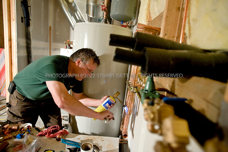 6/23/2008--North Bend, WA, USA..Gerard Maloney of Earthheat working on installing a system in a new home in North Bend, WA, about 30 minutes East of Seattle. Earthheat has been installing  ground-source heat pumps for nearly 10 years; sometimes called geothermal heat pumps, they are heating and cooling systems that can save building owners between 25-65% on their energy costs, with commensurate reductions in carbon dioxide emissions...Here Maloney is working on the water to water ground source heat pump. Behind is the storage buffer tank and in the back left are ducts leading up from chilled water air handler that provides cooling to the house...©2008 Stuart Isett. All rights reserved.