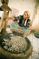 A Uyghur woman is carefully reeling the strands from boiling cocoons of silk worms in a traditional silk workshop in Hotan (Khotan). Atlas is the Uyghur word for silk, and the multi-colored tie-dyed silk fabric worn by many Uyghur women is called Khan Atlas. Hotan was an important oasis town along the ancient Silk Road and visited by Marco Polo on his way to Beijing..
