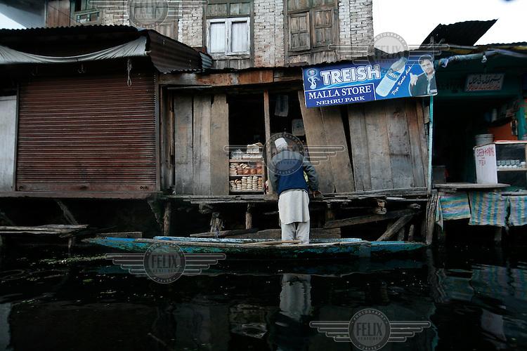 A man in his cano visits a small shop on Dal Lake. Srinagar, Kashmir, India. © Fredrik Naumann/Felix Features