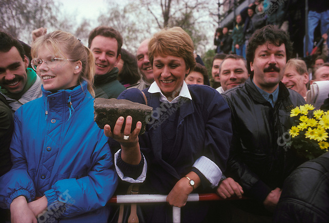 Opening of the Berlin Wall. A West German woman holds a piece of the wall. West Berlin, Germany, November 1989.