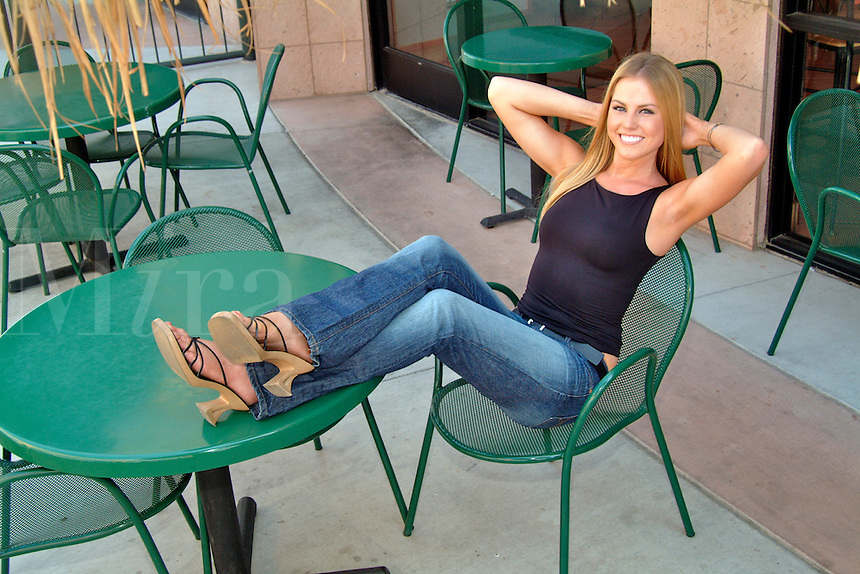 A teenage girl with a big smile and blonde hair wearing a black top and hip hugger blue jeans, sits in a chair on a patio with her feet up on a table