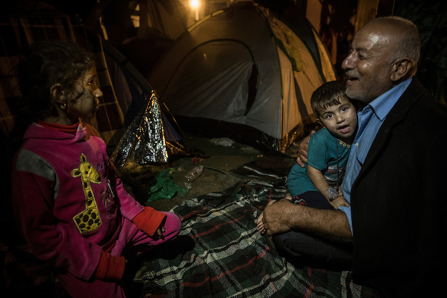A grandfather from Iraqi Kurdistan sings a traditional song to his grandson as the family waited along with thousands of other immigrants for a train from Tovarnik, Croatia towards Hungary and onward towards Western Europe.