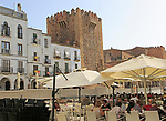 People at cafes in Plaza Mayor near Torre de Bujaco, Caceres, Extremadura, Spain