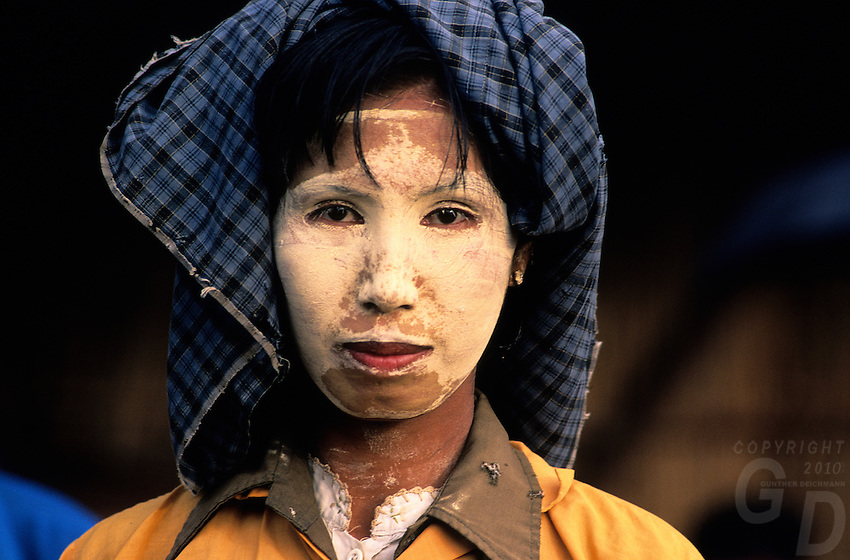 A traditional Burmese, with the typical face paint to show beauty and protect from the sun, Yangon Market, Burma, Myanmar