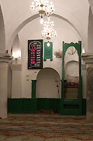 Tripoli, Libya. An-Nagah Mosque, Electronic Digital Clock showing Prayer Times, Qibla, and Minbar (Pulpit).  Tripoli's first mosque, rebuilt 17th Century.