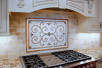 Custom Scrollwork and Fleur, a stone hand cut mosaic, shown in Chartreuse, Travertine Noce, Giallo Reale, Emperador Dark, and Ivory Cream.