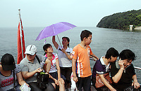 Tourists riding on a boat on Dongting Lake, Hunan Province. Dongting Lake has decreased in size in recent decades as a result of land reclamation and damming of the Yangtze. China. 2010