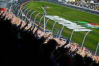 Fans hold 3 fingers aloft on the 3rd lap of the Daytona 500 to remember Dale Earnhardt who died at this race 10 years ago.