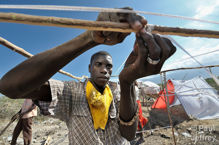 A man fastens sticks together with strips of cloth as he builds a temporary home in a spontaneous camp for quake survivors being established in Croix-des-Bouquets, Haiti, north of the capital Port-au-Prince. Quake survivors continue to move as aftershocks continue, and reports of aid deliveries in one camp will provoke families from other camps to migrate there.