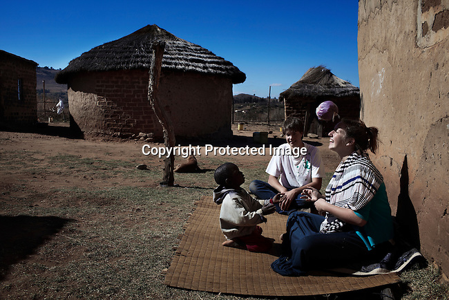 "MBABANE, SWAZILAND - AUGUST 3: German student Julian Storch, age 19, and a friend plays with an orphan while fellow Senior students visit orphans in a village during a community service program called ""young heroes"" at Waterford Kamhlaba United World College of Southern Africa, a secondary school on August 3, 2013 in Mbabane, Swaziland.  Julian grew up with a family with siblings and the family also took care of children and youth. He has a passion for children and likes to work in rural areas with children. (Photo by: Per-Anders Pettersson)"