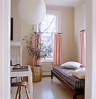 The pink half-curtains reflect the pale pink of the ceiling in the living room