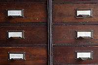 Detail of a series of antique wooden office drawers used for storage in a guest bedroom