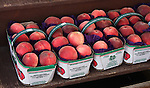 Baskets of 8 peaches at farmstand, Canada.