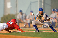 First baseman Diego Cruz #34 of the Burlington Royals waits for the throw as Michael Swinson #10 of the Johnson City Cardinals dives back to the bag at Howard Johnson Stadium June 27, 2009 in Johnson City, Tennessee. (Photo by Brian Westerholt / Four Seam Images)