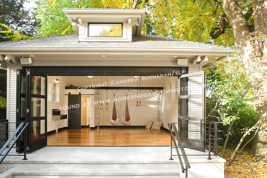 A wall of sliding doors opens wide to a large play space full of gymnastics equipment in this unique backyard play pavilion.