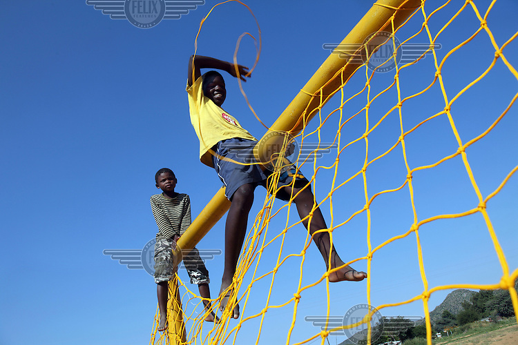 13 year old Advivro Johston secures a net to a goal's crossbar in preparation for an upcoming match.