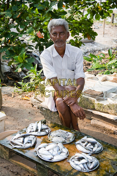 Man selling fish on the pavement, Fort Cochin, Cochin, Kerala, India