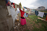 """A woman refugee from Syria puts her laundry out to dry. She lives with her family in a rented """"tent""""--made from a billboard canvas of a dollar bill--in the village of Jeb Jennine, in Lebanon's Bekaa Valley. They and other refugee families in the area are being assisted by International Orthodox Christian Charities and other members of the ACT Alliance.."""