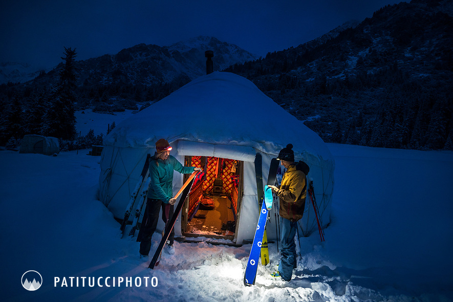 Putting skins on skis outside a yurt at dawn, using headlamps, while on a ski touring trip in the Aksuu Valley of Kyrgyzstan