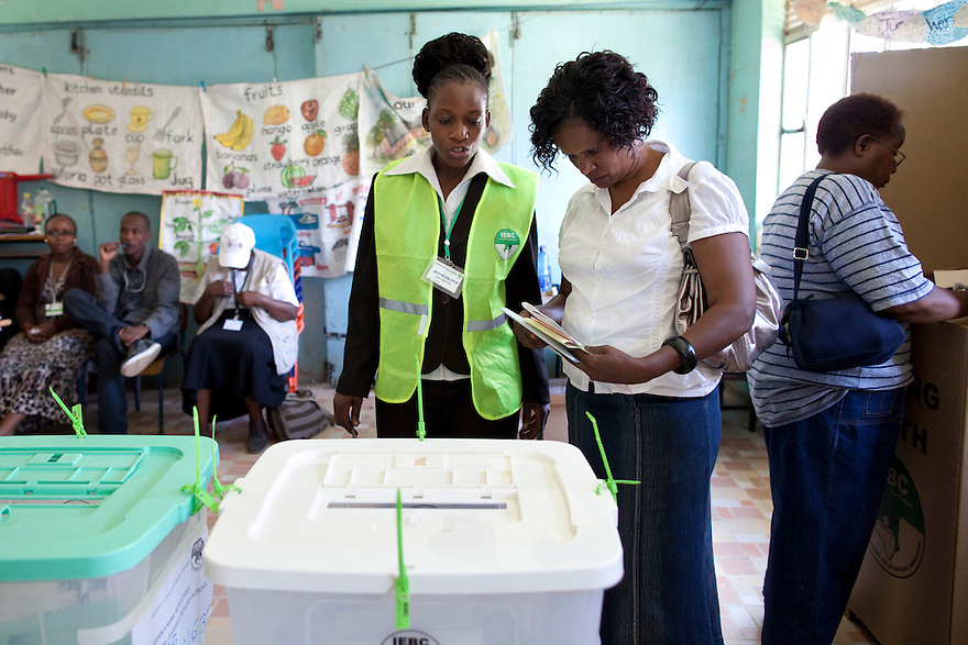4 March 2013 - Nairobi, Kenya - An Independent Electoral and Boundaries Commission (IEBC) official helps a woman to cast her vote at a polling centre during the Kenyan general elections in Nairobi, Kenya. Five years after more than 1,000 people were killed in election-related violence, Kenyans began casting votes in a nationwide election seen as the country's most important, and complicated, in its 50-year history. Uhuru Kenyatta, one of two top candidates for president, faces charges at the International Criminal Court for orchestrating the 2007-08 postelection violence. Photo credit: Benedicte Desrus