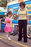 Berkeley CA  Preschool teacher helping student balance on balance beam in class.