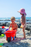 A local boy and girl play at a beach in Puako, South Kohala, Hawai'i Island.