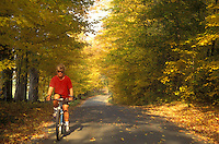 biking, woman, country road, fall, East Montpelier, VT, Vermont, Woman biking on a country road surrounded by colorful fall foliage in East Montpelier in the autumn.