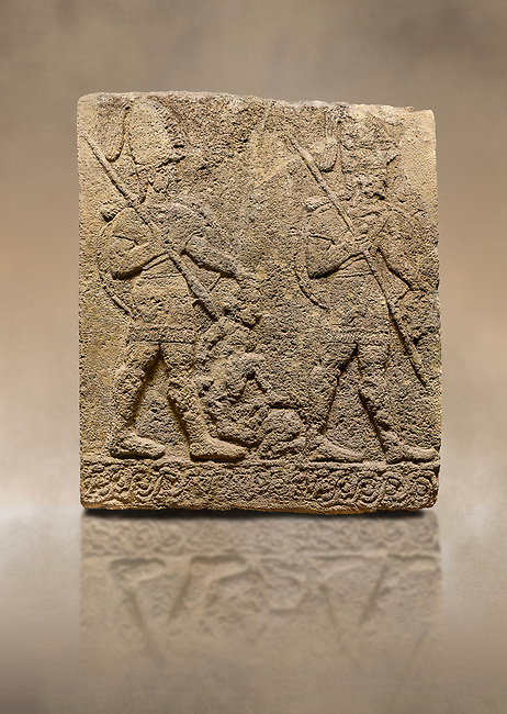 Photo of Hittite sculpted Orthostats panel of Long Wall Limestone, Karkamıs, (Kargamıs), Carchemish (Karkemish), 900-700 B.C. Soldiers. Anatolian Civilisations Museum, Ankara, Turkey<br /> <br /> Figure of two helmeted warriors. They have their shield in their back and their spear in their hand. The prisoner in their front is depicted small. A human head is depicted in the left hand of the warrior in the front. The warrior at the rear holds the prisoners sitting on his lap from his hair. Below this figure, which was described small, lies yet another small human figure. <br /> <br /> On a brown art background.