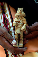 Wally Grover carrying a piece of wood and a pocket knife is his answer to working at home. Whenever he finds a few minutes he carves. This raw beginning is shown in the after photo painted up and detailed as a Owl Kachina.