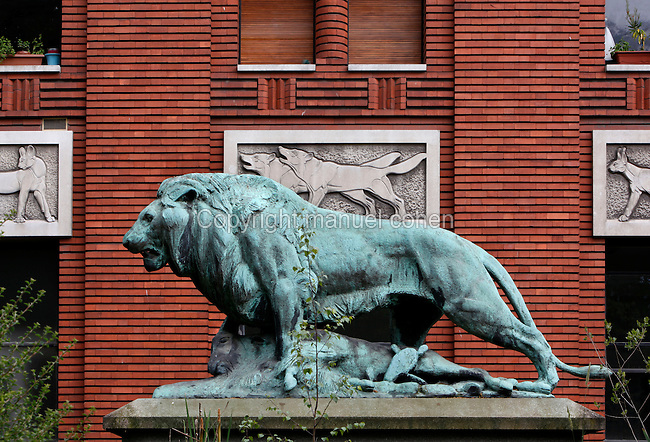 General view of the statue called Lion tuant une chevre or Lion et mouflon (Lion killing a goat), created by Paul Jouve circa 1937 and located in front of the Art Deco Fauverie (the big cats building) built by Rene Berger, in the Menagerie of Jardin des Plantes, Paris, 5th arrondissement, France. The bronze statue of the Lion tuant une chevre was cast by the Fonderie Rudier, a foundry created in 1792 and also producing Auguste Rodin, Aristide Maillol and Antoine Bourdelle master pieces. Founded in 1794 by Jacques Henri Bernardin de Saint-Pierre, the Menagerie of Jardin des Plantes became the largest exotic animal collection in Europe in the 19th century and is the second oldest public zoo in the world. Picture by Manuel Cohen