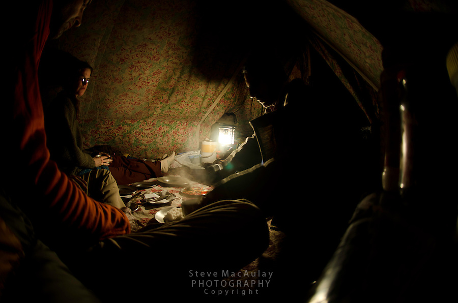 Interior view of Kashmiri trekking tent with travelers eating a meal with guide, Western Himalayan Mountains,  Kashmir, India.