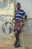 Ethiopia. Southern Nations, Nationalities, and Peoples' Region. Omo Valley. Turmi. Hamar tribe (also spelled Hamer). Pastoralist group. A young man stands close to  a school with a world globe drawn on the wall. As a custom, every Hamer man carries a wooden headrest which doubles as a stool. The Omo Valley, situated in Africa's Great Rift Valley, is home to an estimated 200,000 indigenous peoples who have lived there for millennia. Amongst them are 60'000 to 70'000 Hamar, an Omotic community inhabiting southwestern Ethiopia. They live in Hamer woreda (or district), a fertile part of the Omo River valley, in the Debub Omo Zone of the Southern Nations, Nationalities, and Peoples Region (often abbreviated as SNNPR) which is one of the nine ethnic divisions of Ethiopia. 9.11.15 © 2015 Didier Ruef
