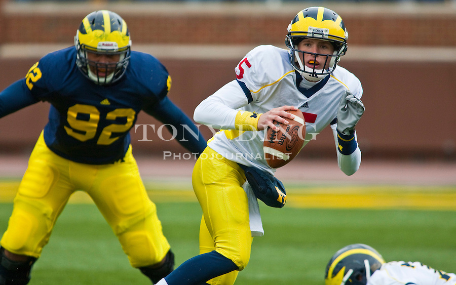 Michigan quarterback Tate Forcier (5) evades defensive tackle Greg Banks (92) during the Wolverines' spring football game, Saturday, April 17, 2010, in Ann Arbor, Mich. (AP Photo/Tony Ding)